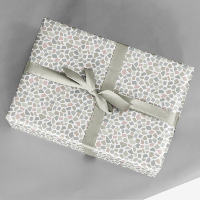 present wrapped in soft neutral torn paper collage gift wrap with ribbon