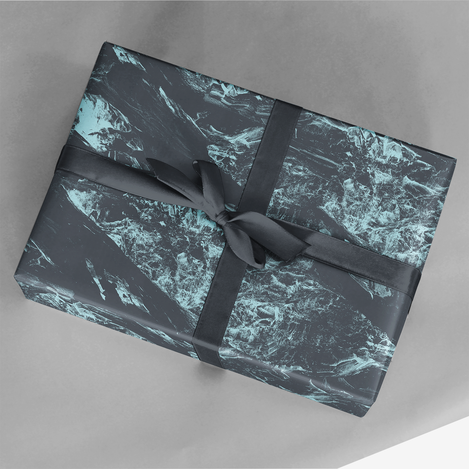 present wrapping in rugged bluish land-textured terrain gift wrap with rich ribbon