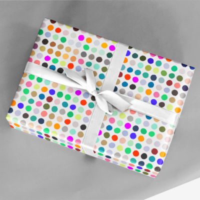 gift wrapped in vegetable stamp gift wrap with rainbow colored polka dots and a silver ribbon