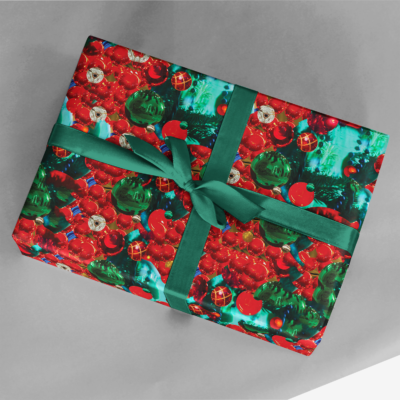 gift wrapped in red and green holiday ornaments wrapping paper with green ribbon